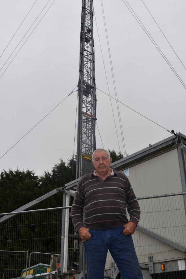 Pensioner Paul Smith in front of the 20-metre-high mast in his back garden