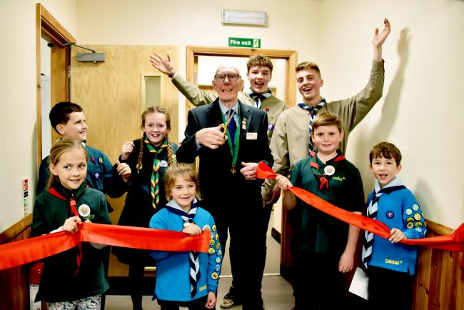 Wyre Forest Scouts president John Beard cuts the ribbon to open the new facility with the help of Beavers, Cubs, Scouts. PIC: Colin Hill