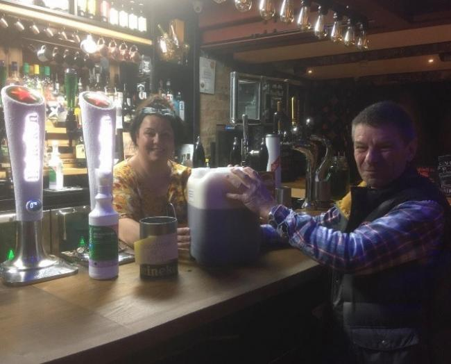 Staff at Worleys at The Swan in Stourport filling visitors' containers with ale in exchange for a donation to KEMP