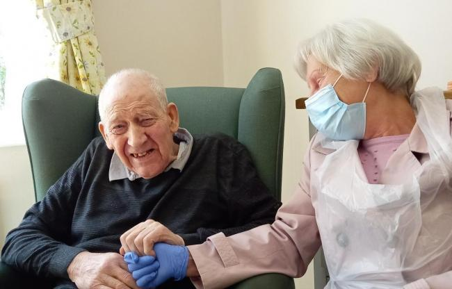 Hollyfields resident Peter Underwood holds hands with his wife of 61 years Jill for the first time in over a year