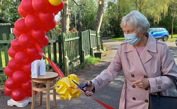 Kidderminster Shuttle: Jill Underwood cuts the ribbon outside Hollyfields Care Home in Kidderminster before being reunited with her husband Peter