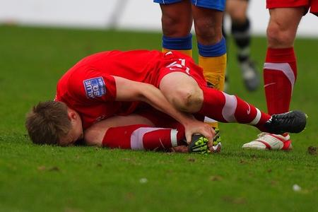 Tom Shaw holds his foot in agony after a clash with Mansfield's Niall O'Rafferty.
