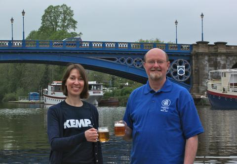 Bottoms up: Ele Millward and Nick Yarwood sample the beer by Stourport's historic River Severn bridge.