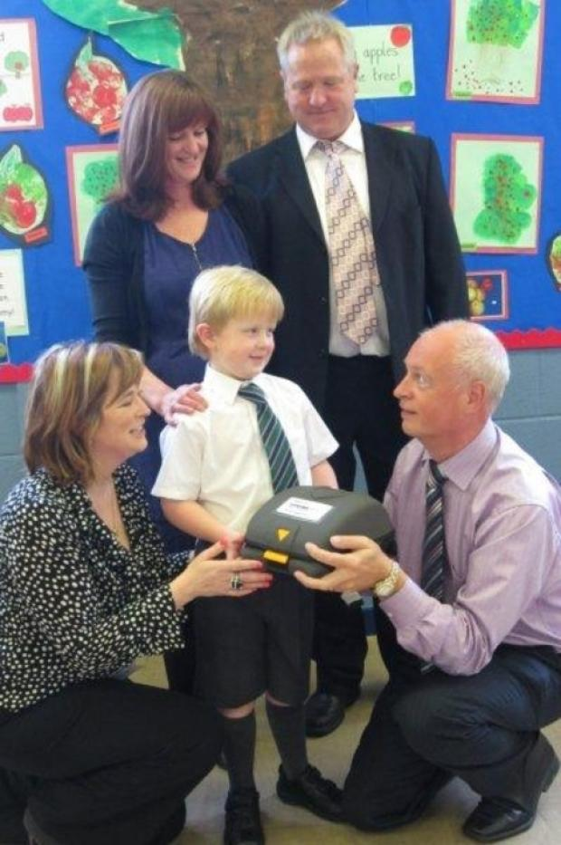 Hand on heart: William Wallace being handed the defibrillator, with, clockwise from left, Jo Bradley, his parents Lorraine and Lloyd Wallace and headteacher Nigel Humphreys.
