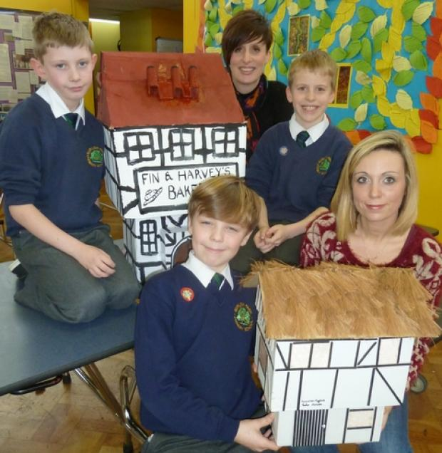 Creative display: Clockwise from front right, Lisa Richardson with her son Finley, Harvey Mathews and Melinda Taylor with her son Cameron, with the houses.