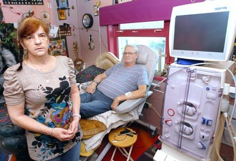 Home loss fears: Elaine and Bryan Tudor in his bedroom with the dialysis machine.