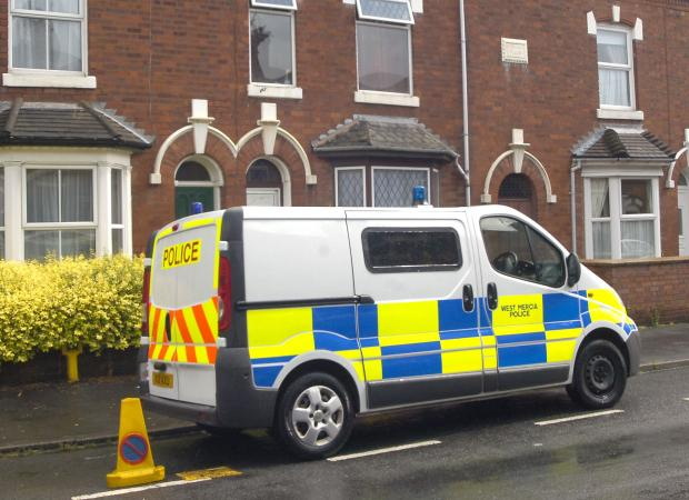 On guard: A police van outside the property in which a woman was found stabbed.