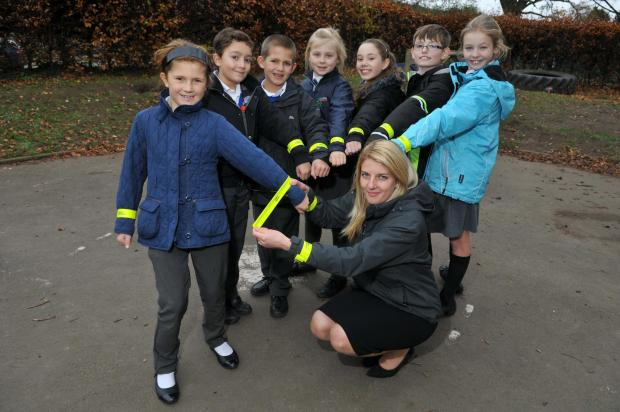 Standing out: Lickhill Primary School teacher Kelly Lewis, front, centre, with pupils try on the new bands.