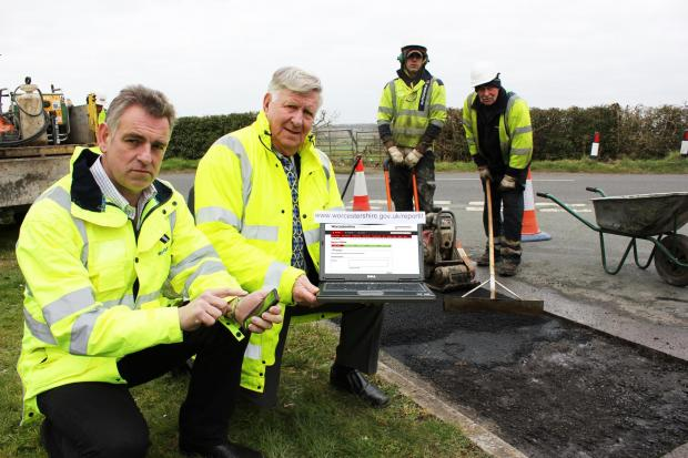 FILLING IN: Jon Fraser, left with Councillor John Smith join a repair gang fixing potholes.