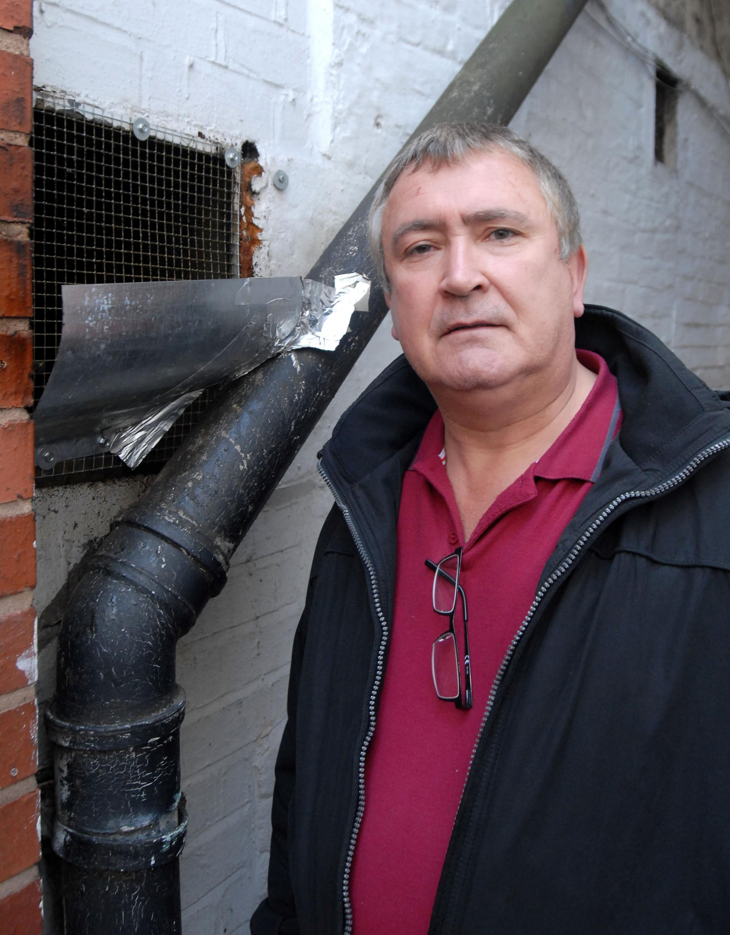 ODOUR COMPLAINT: Adrian Mayall standing next to the extractor fan he is complaining about.