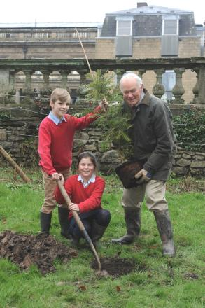DIGGING IN: Pupils Jake Price and Eliza Corrie with Abbey Forestry director Bede Howell and the Woollemi Pine.