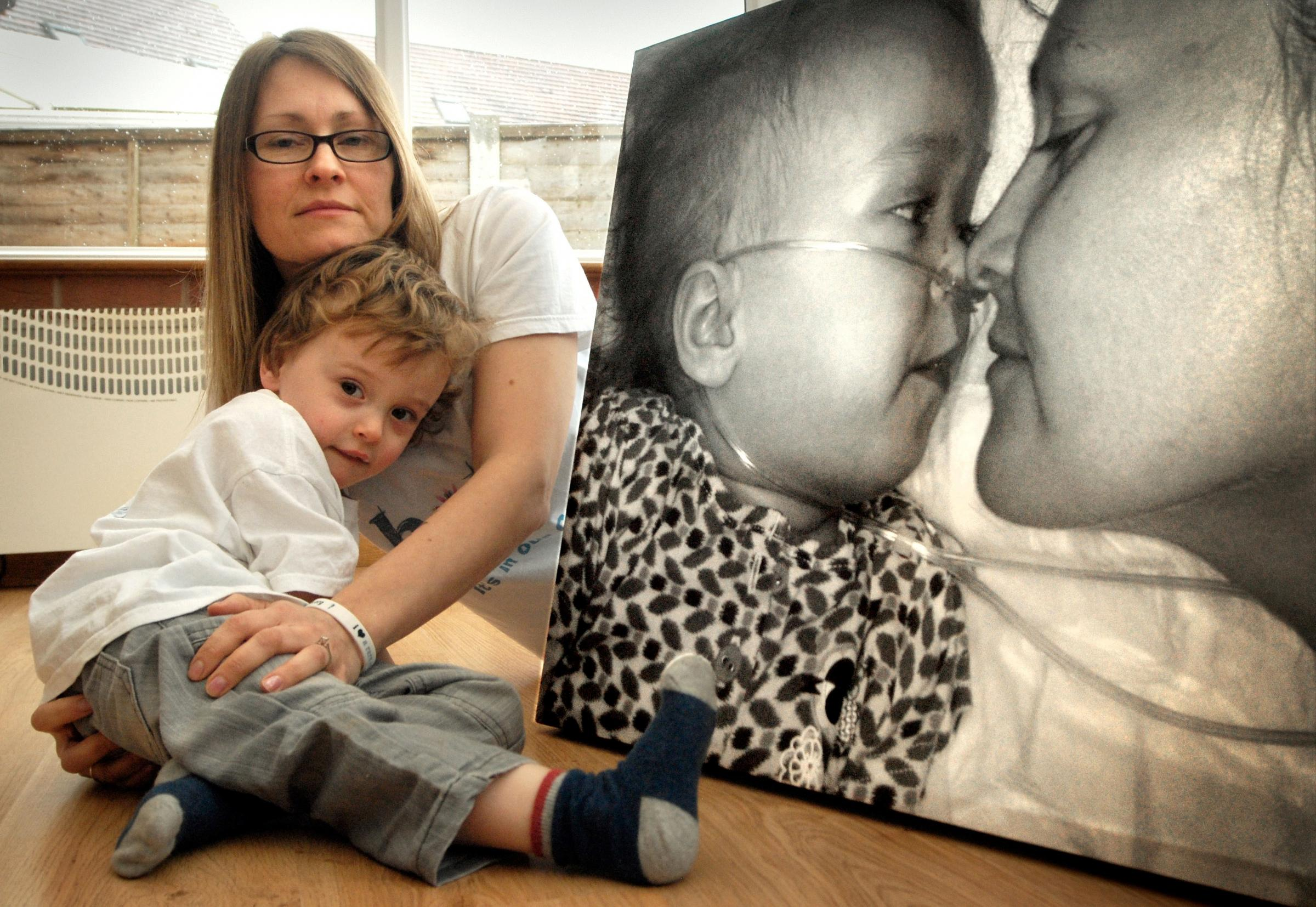 LIKE A BUTTERFLY: Nikki Backus and her son Sam, three, with a photograph of his twin sister Ruby.