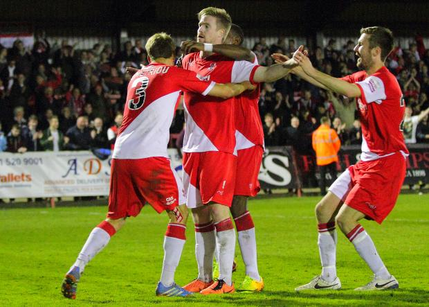 Michael Gash takes the plaudits from teammates after his goal against Cambridge on Tuesday.