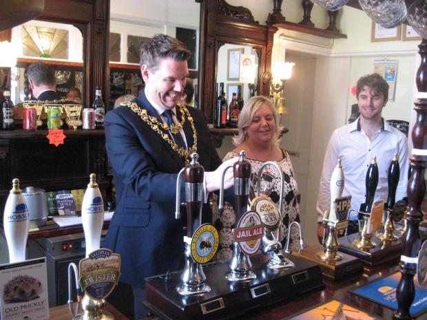 OPEN FOR BUSINESS: Mayor of Kidderminster John Campion helps landlady Lisa Harvey to pull the first pint, with Richard Davis, right.