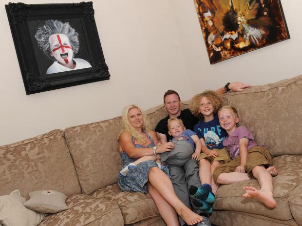 PROUD: Jody Craddock with, from left, wife Shelley and sons Toby, Joseph and Luke, with some of his artwork behind them.