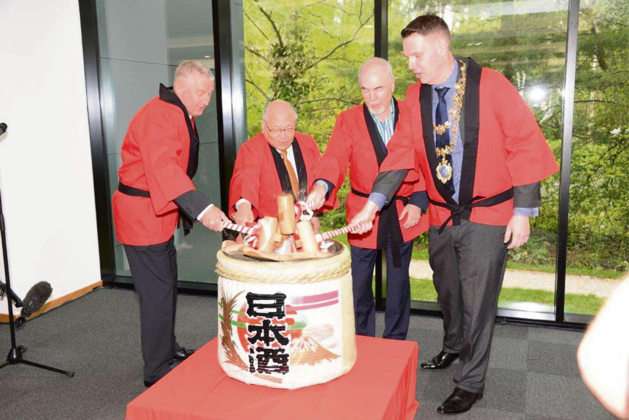 GRAND OPENING: From left, Amada general manager Steve Basford, Mitsuo Okamoto, managing director of partner Hallmark Sheetmetal Paul Martin, and John Campion in a display of Taiko drumming.