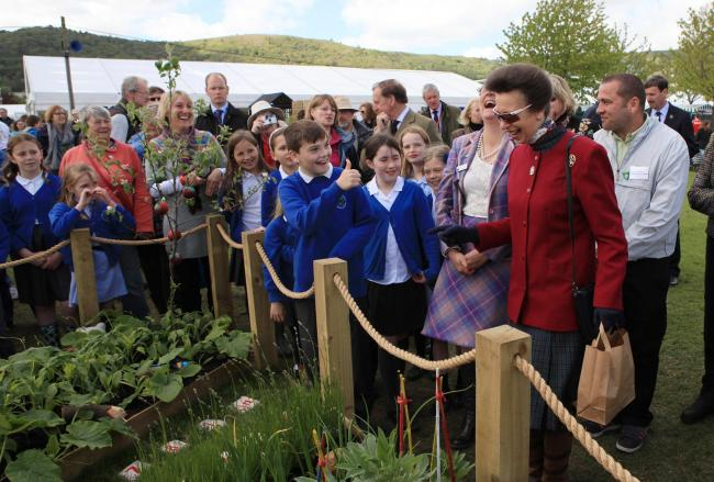 THUMBS UP: Abberley Parochial Primary School pupil Josh Cook makes Princess Anne laugh at RHS Malvern Spring Festival.