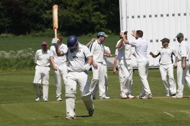 Walk of shame: Stourport skipper Craig Siwicki returns to the pavilion as Chaddesley Corbett's players celebrate taking his wicket. Picture: CRAIG ROSS