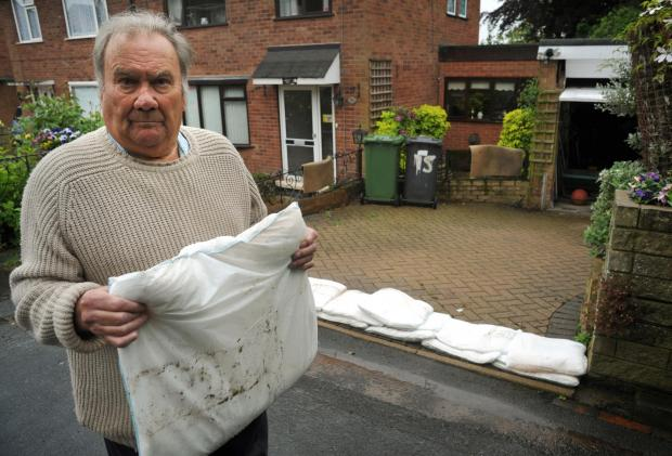 TAKE ACTION: Ray Kilgour lays out sandbags to stop flood water reaching his Princess Way home. Picture: Phil Loach. 231401L