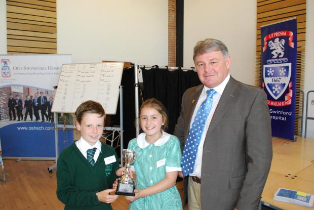CHALLENGE COMPLETE: Winning pupils Freddie Nock and Jessica Shaw collecting their trophy from Peter Jones.