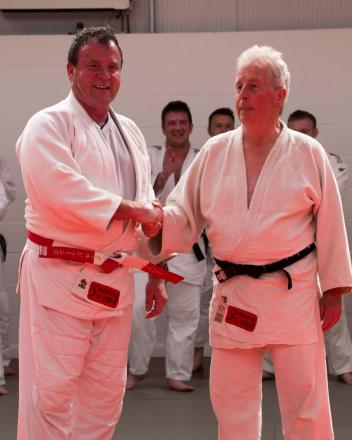 A meeting of Samurai legends: Paul Jones (left) receives his sixth dan belt from John Maguire during the club's 35th anniversary celebrations.