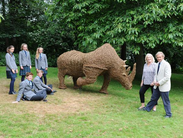 PECULIAR PRESENT: John Walker, right, and wife Janie, with some of the final year pupils who helped to create a wicker rhino statue.