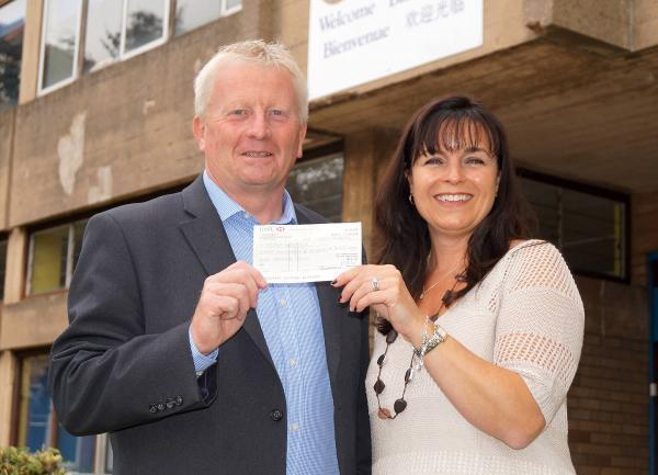 SCHOOL DONATION: Michelle Howles, chairman of Holy Trinity School PTA, presents a cheque to Kemp Hospice's Kevin Hateley.