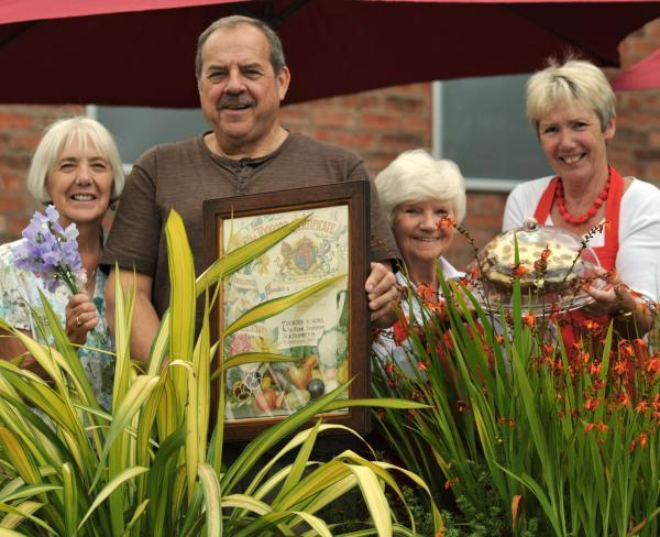 GREEN FINGERS: Diane Chater, publicity secretary, Stuart Williams, club secretary and Connie Jones and Sue Humphries, St George's Hall volunteers, prepare for the Flower, Vegetable and Floral Art Show. 311429L