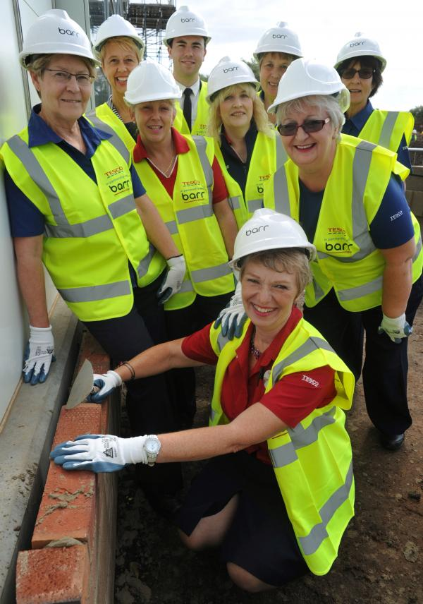 BRICK LAYERS: Jill Pardoe, front, lays her brick watched by store manager Chris Collins, top centre, with Sue Jarrett, Emma Williams, personnel manager, Pam Philpotts, Penny Oliver, Pat Cole, Angela Godfrey and Marlene Sandford. 321429L