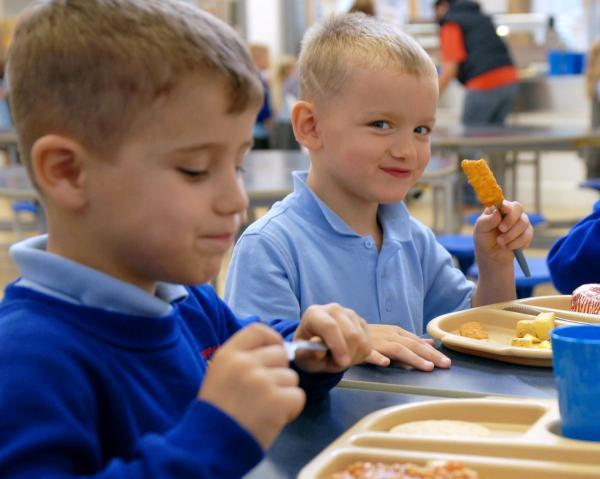 FREE FOOD FOR PUPILS: Logan Butcher and Cayden Hemming, both five, tuck into their first free school meal.