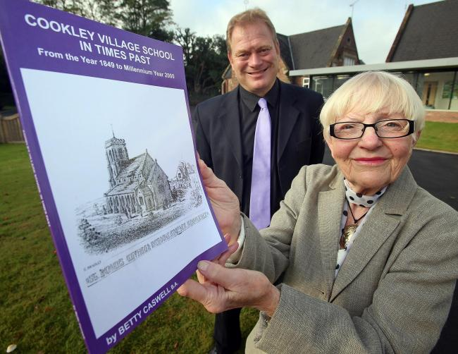 LOOKING BACK: Betty Caswell and Cookley Sebright Primary School headteacher Martin De Vine with Betty's latest village history book. 431407JH