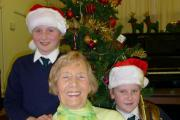 CHRISTMAS CHOIR: Burlish Park pupils Harriet Ferris, and Aimee Hartin with centre visitor June Whiteman-Haywood.