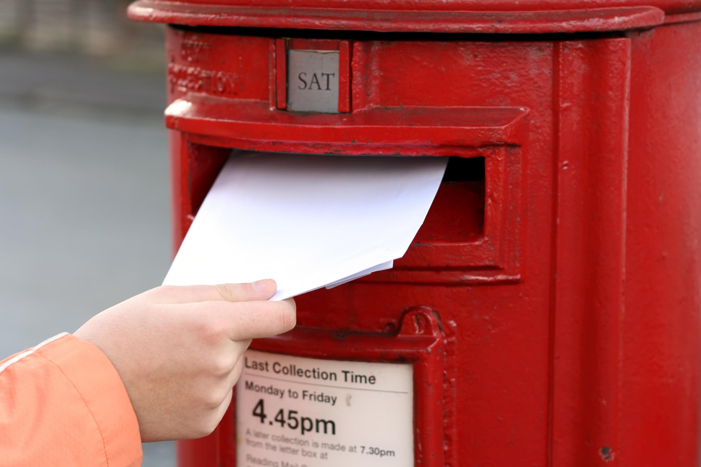 posting letter to red british postbox on street