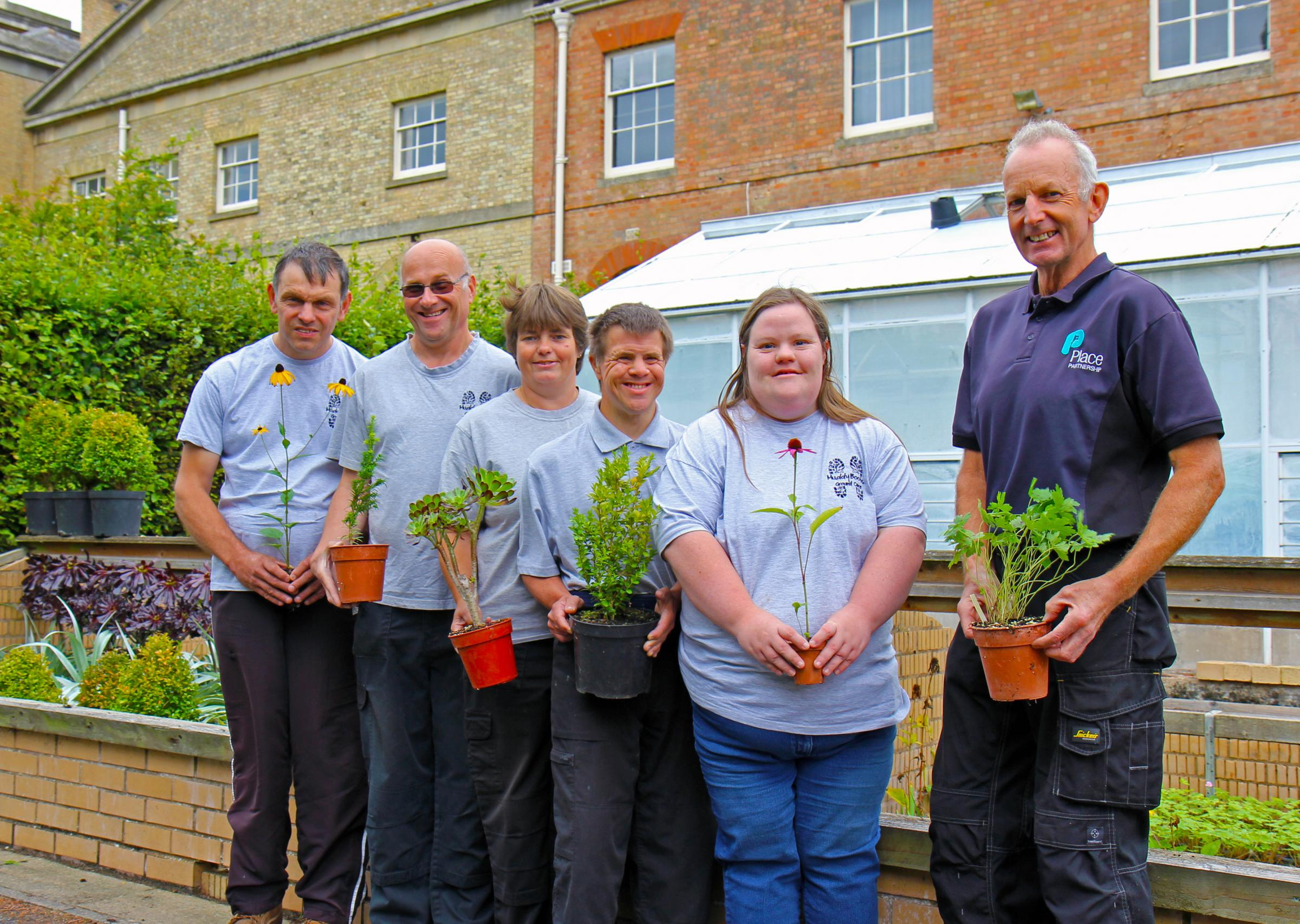 Place Partnership's head gardener Stuart Reading (Right) with members of Muddy Boots