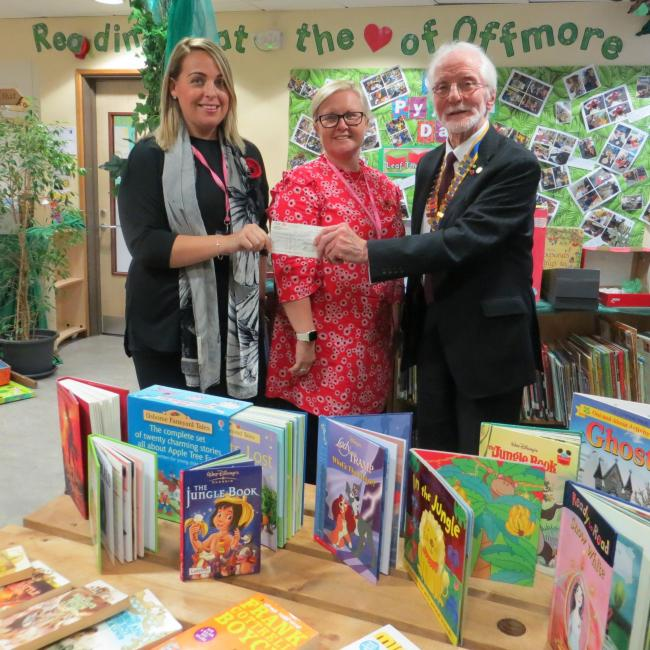 The President of Kidderminster Rotary Club, Bill Crook, with Kirsty Bayliss and Gemma Brown at Offmore Primary School and books donated by the Rotary Club.