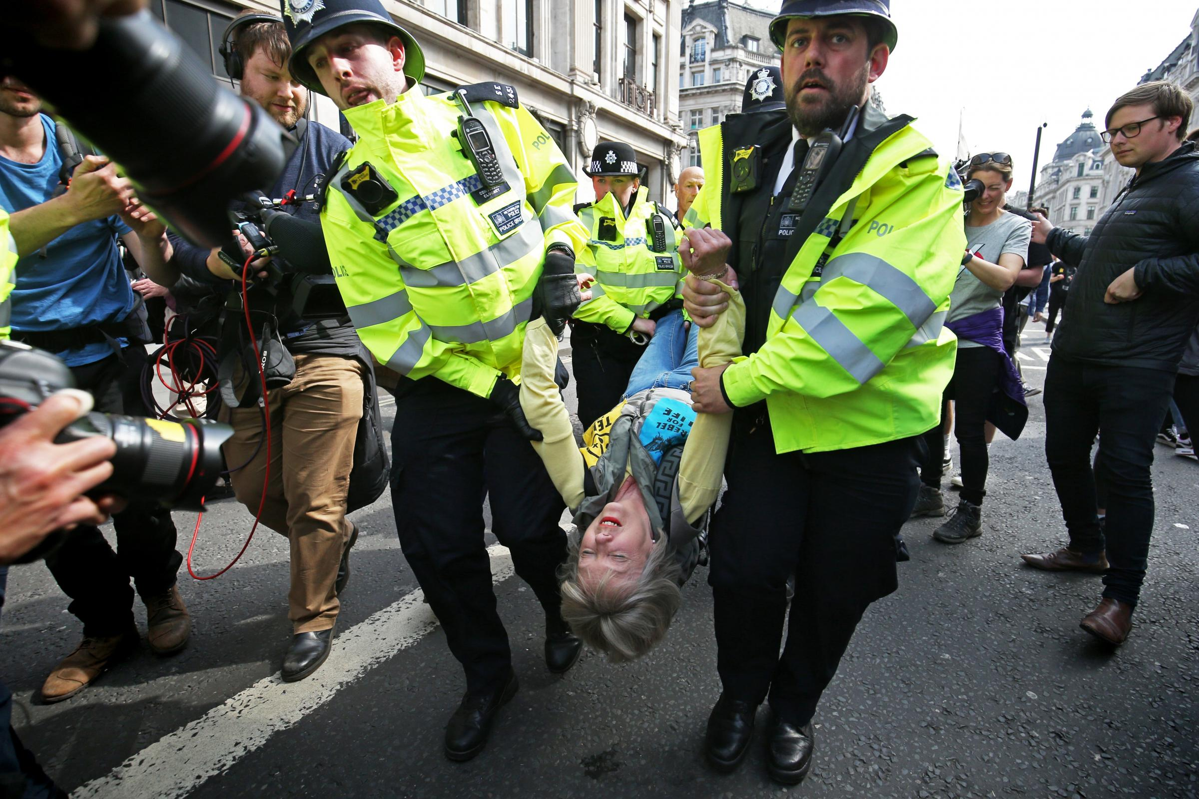 An Extinction Rebellion demonstrator is carried away by police at Oxford Circus