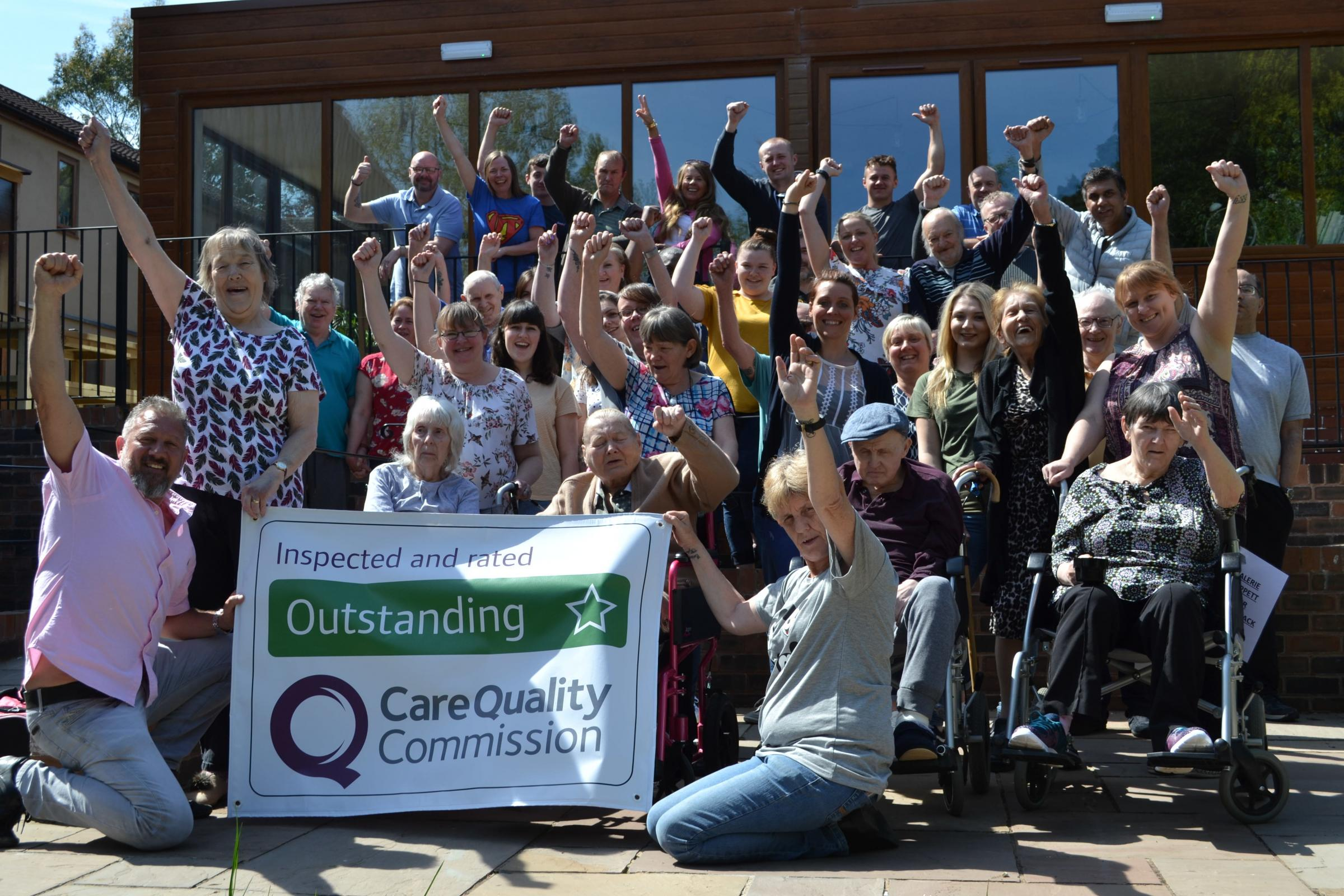 Staff and residents at Casa Mia Care Home celebrating their 'outstanding' CQC rating